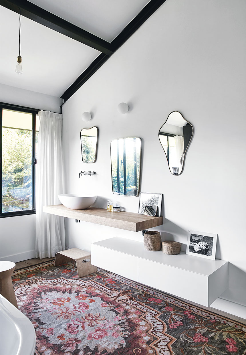 Oriental rug, various mirrors and wood stool inside of a stylish bathroom