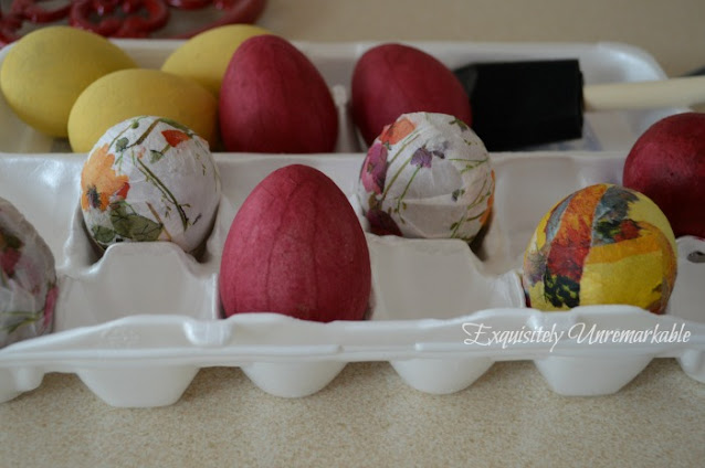 Decoupaged and painted eggs in a carton