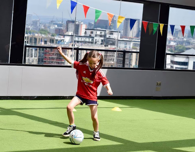 Girl in Manchester United kit playing football