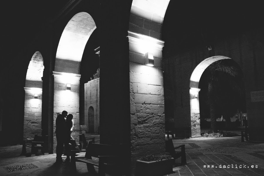 pareja de novios se besan en la noche bajo los arcos iluminados
