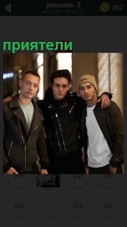 В помещении стоят трое парней, приятели в обнимку друг с другом