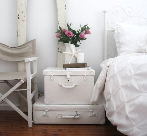 This simple white vintage suitcase makes the perfect coastal bedside table.