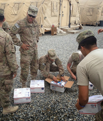 U.S. Soldiers opening up care packages from the Airborne Angel Cadets of Texas.