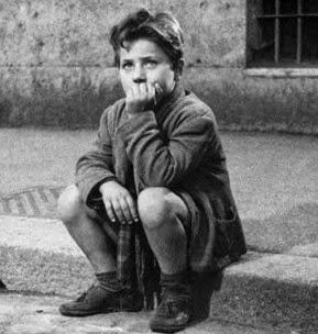 Fotograma de la película: Ladrón de bicicletas. En blanco y negro, se muestra al niño esperando, pensativo, a su padre, sentado en el borde de la acera de una calle de Roma