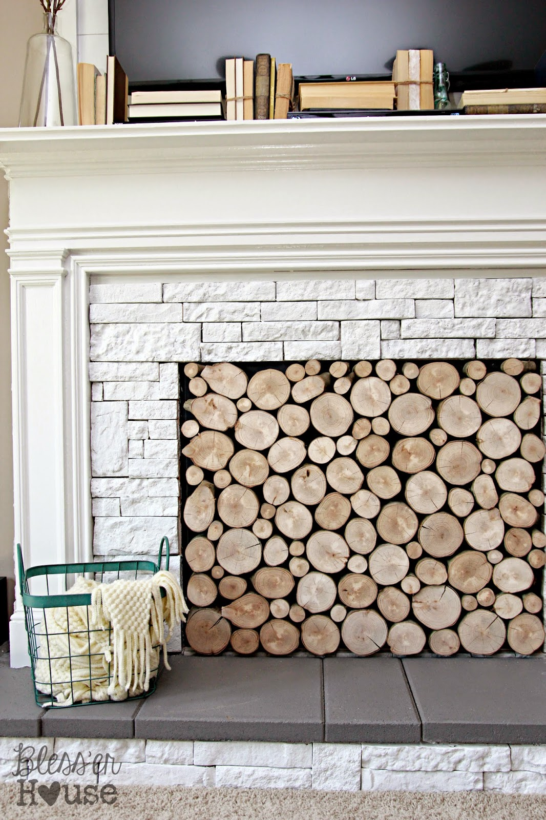 DIY Faux Fireplace Makeover...It looks like the fireplace is filled with wood.  Genius!  (From Bless'er House) | Friday Favorites at www.andersonandgrant.com