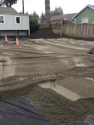 Fresh topsoil has been spread in a backyard. Tractor tread tracks criss cross the newly spread soil.
