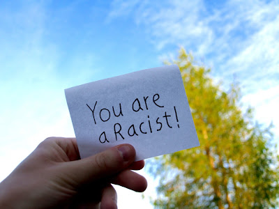 "A hand holding a white card that says, ""You are a racist!"""