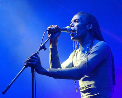 The Beat's Ranking Roger singing on stage as he holds the microphone and stand.