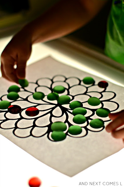 Preschool child placing glass stones on a flower mandala on the light table