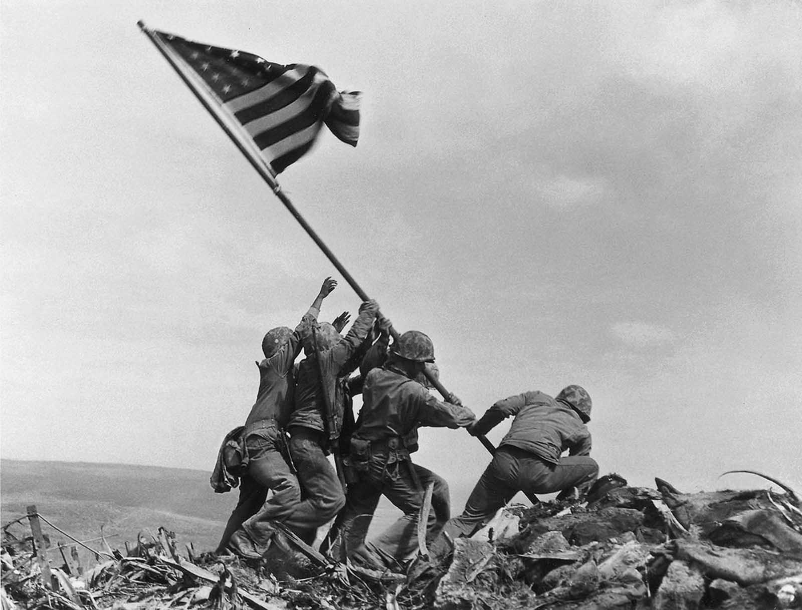 U.S. Marines of the 28th Regiment of the Fifth Division raise the American flag atop Mt. Suribachi, Iwo Jima, on February 23, 1945. The Battle of Iwo Jima was the costliest in Marine Corps history, with almost 7,000 Americans killed in 36 days of fighting.