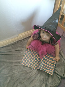 sophia reading halloween book dressed as a witch