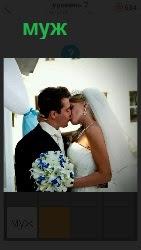 невеста с цветами целуется с женихом
