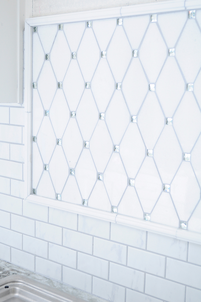 White shaker kitchen cabinets with lucite pulls and thassos reflection marble tile backsplash. | via monicawantsit.com
