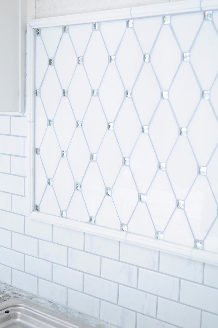 White shaker kitchen cabinets with lucite pulls and thassos reflection marble tile backsplash. | via monicawantsit.com