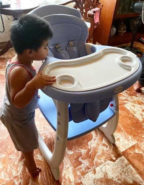 A cute toddler inspecting a high chair