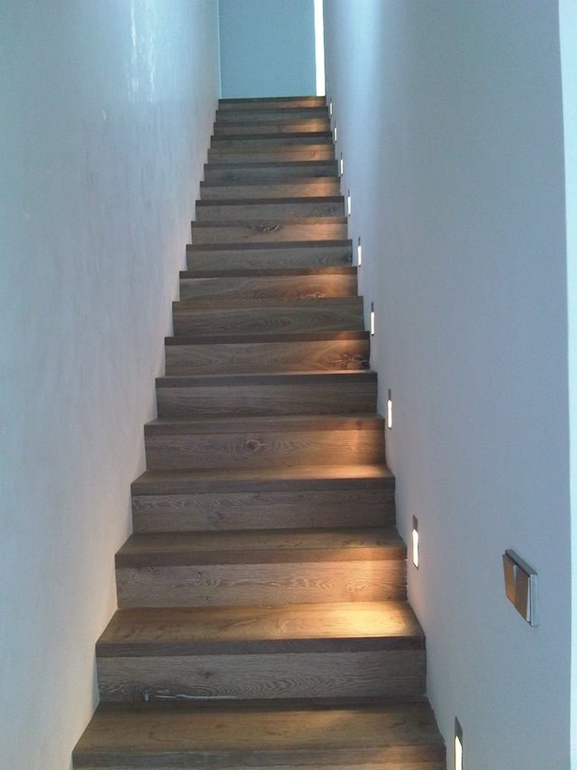 Narrow wooden stairs with floor lighting