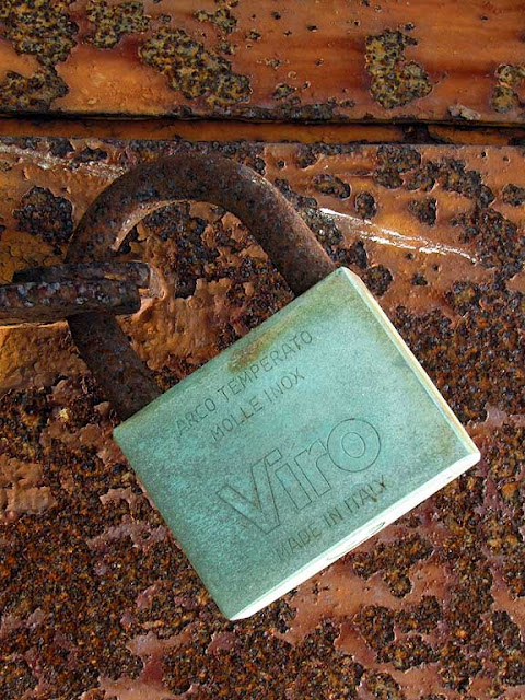 Steel rust and brass oxidation against a background of rusted iron, port of Livorno