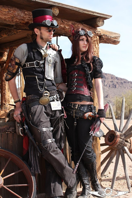 Steampunk couples costume, weird west, wild west fest. man and woman in red and black steampunk clothing.
