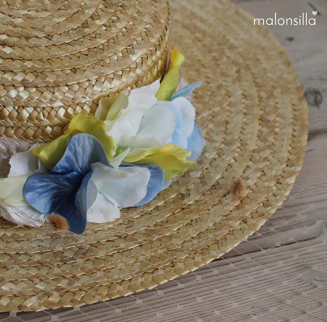 Vista en detalle del sombrero de paja para boda con flores de tela.