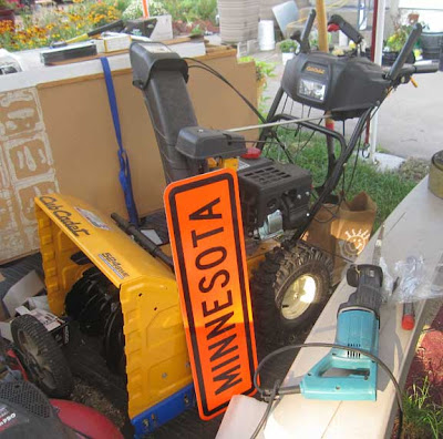Yellow snowblower with an orange road sign that says Minnesota, leaning against it