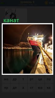 на причале за канат закреплено судно, стоящее рядом с пирсом