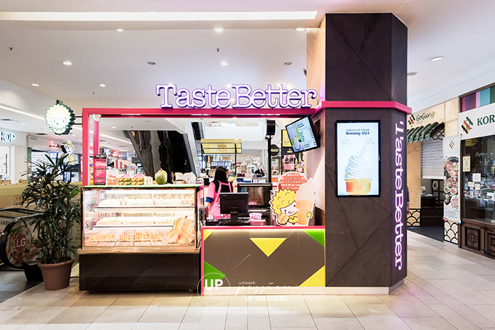 taste better empire subang kiosk column wrapped in dark grey stone texture and wood texture laminate with TV menu and striking corporate pink color metal structure for highlight