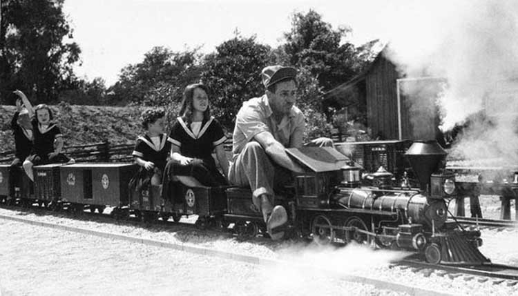 Walt Disney takes a ride on his backyard train