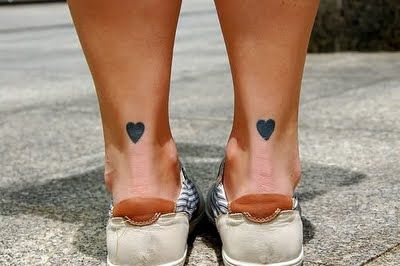 Tatuajes en tobillo de una chica, cada uno con un corazon tribal pequeño de estilo tr