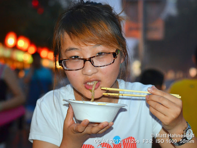 China; Beijing; Donghuamen Night Market; Chinese woman slurping noodles; Chinese food delicacies; chop sticks; Matt Hahnewald; Facing the World; portrait; street portrait; food; noodles; noodle soup; night; bokeh; travel; travel destination; tourism; eyeglasses