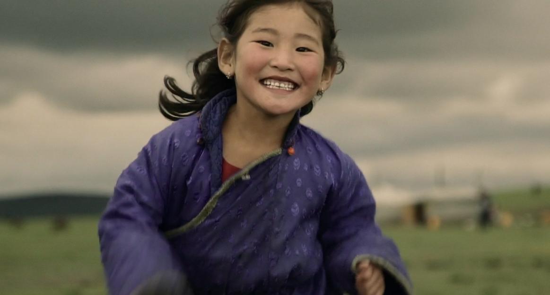 Ein mongolisches Mädchen rennt freudestrahlend auf den Betrachter zu.