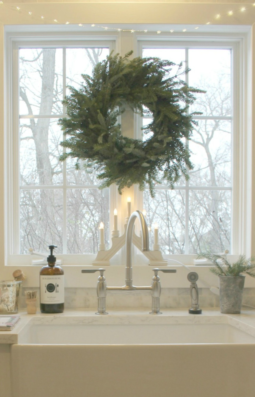 White modern farmhouse kitchen decorated for Christmas with wreath over farmhouse sink. Come be calmed by How to Freak Less About Holidays, Decorating and Gifts as well as Entertaining.