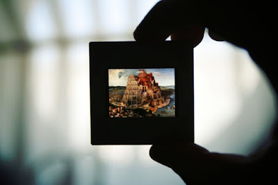 Shadowy hand holding a color slide with a reproduction of Bruegel's painting of the Tower of Babel.