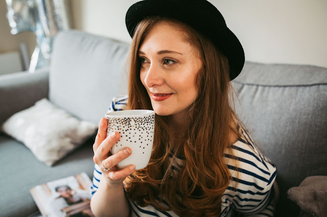 girl sitting on sofa, holding coffee mug and smiling