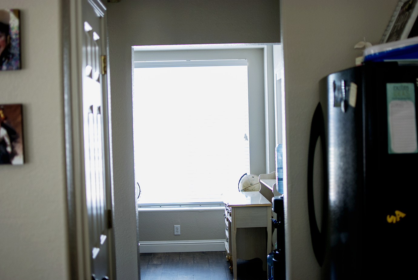 View of office from the kitchen - hardwood floors installed and fresh light gray paint on the walls
