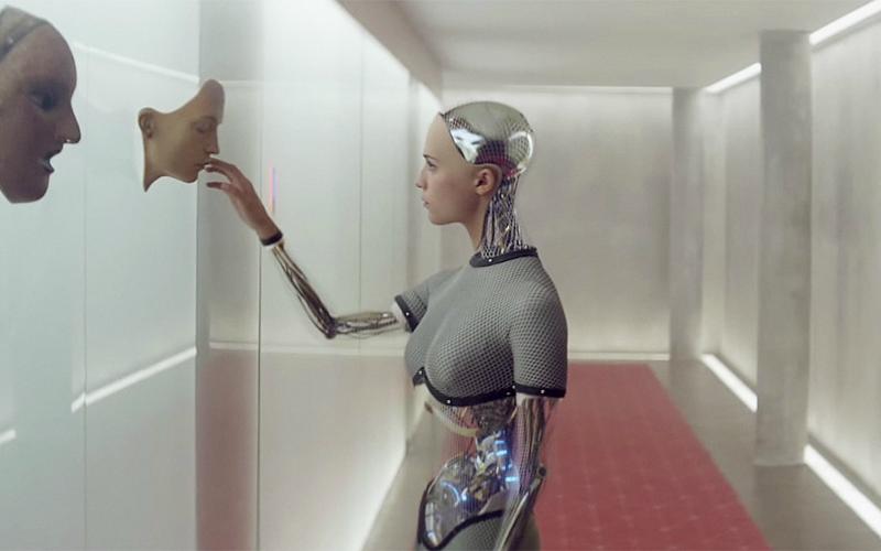 Na imagem: uma mulher robótica, com apenas mãos e rosto aparentemente humanos, toca numa face como a dela pendurada na parede.