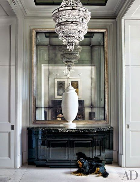entryway with antique mirror and chandelier