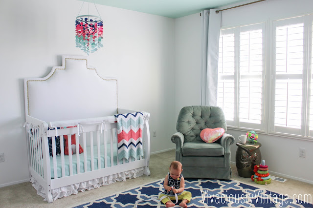 Mint green coral & navy nursery. Upholstered crib