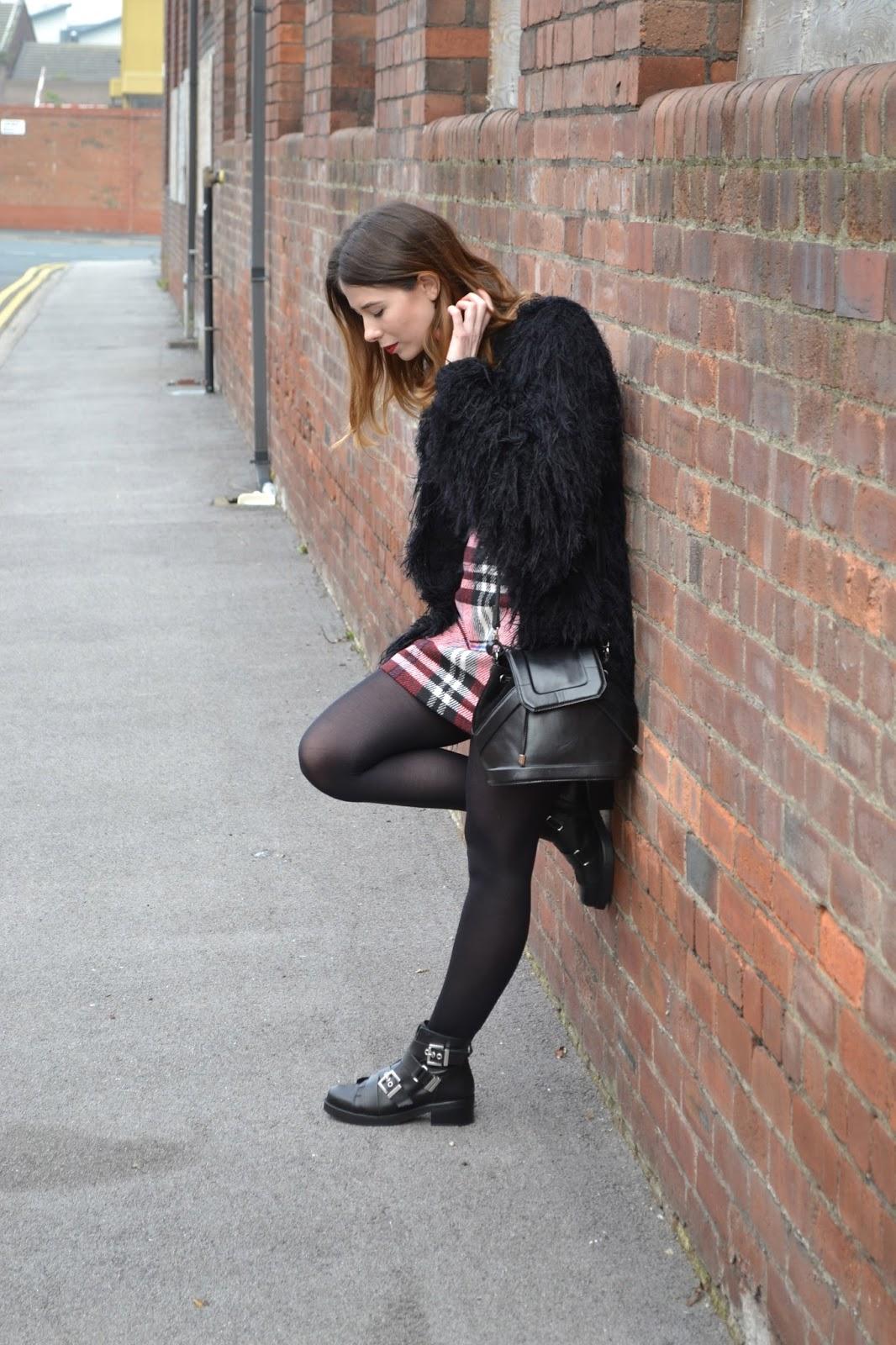 womens affordable highstreet fashion blog featuring British street style. Black polo neck. Topshop tartan skirt. Leather black buckle boots from Kurt Geiger. Black shabby jacket. Hollies closet