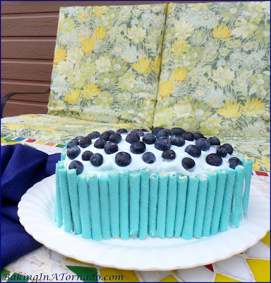 Berry Blue Angel Poke Cake, an angel food loaf infused with blueberries and raspberry liqueur then frosted with flavored whipped cream. | Recipe developed by www.BakingInATornado.com | #recipe #dessert #cake #blueberries
