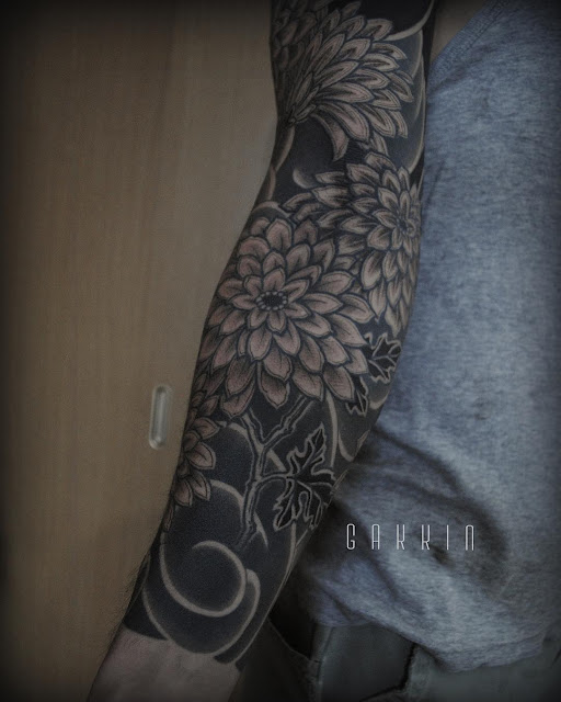 an interesting tattoo design, covering the whole arm with floral patterns