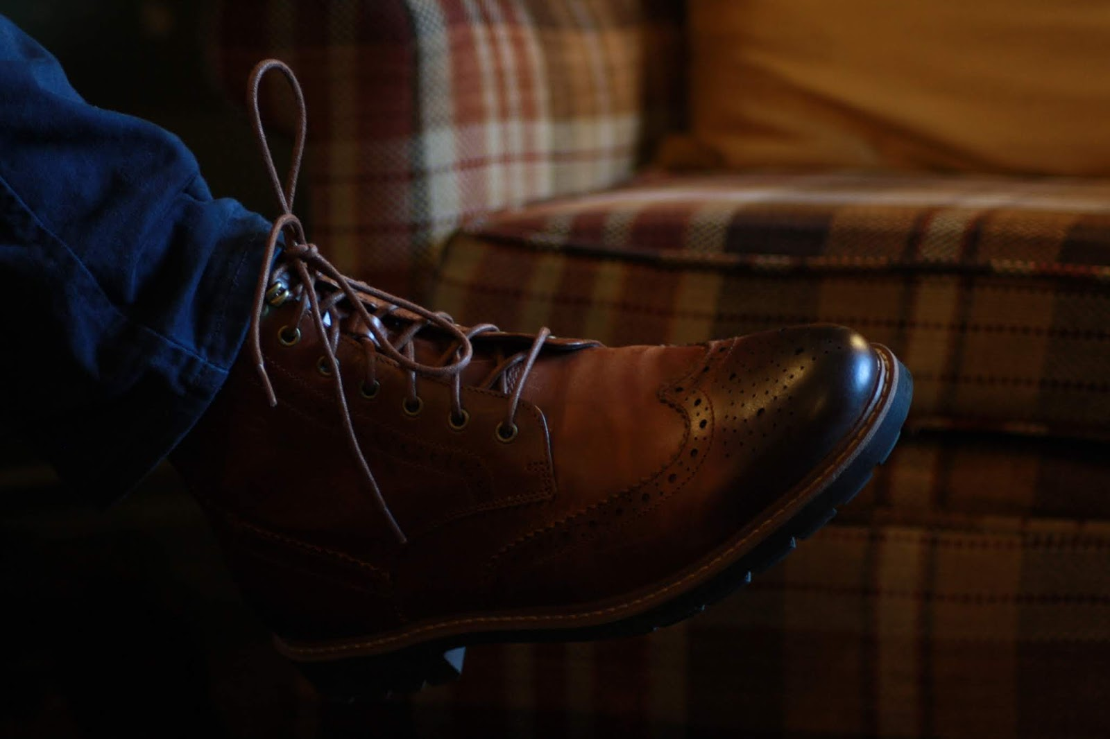 close up of dark tan lace-up boot and dark blue trouser leg, a checked chair in the background