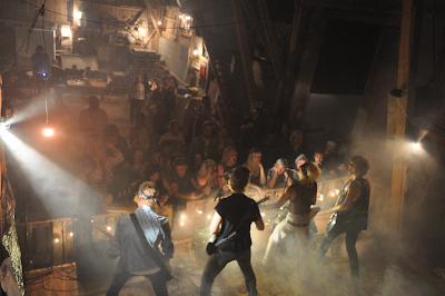 Konsertbild från Elinorspelen med bandet sett bakifrån och publik framför scenen.