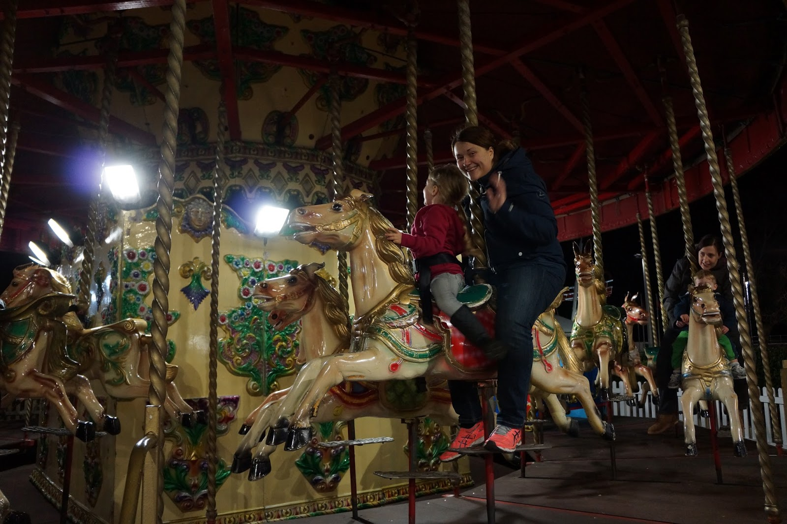 mum and daughter riding a horse on a merry go around at dark at butlins minehead