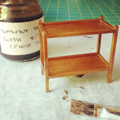 Stained modern miniature tea trolley on a workbench with a jar of diluted walnut stain  next to it and a brush in front of it.