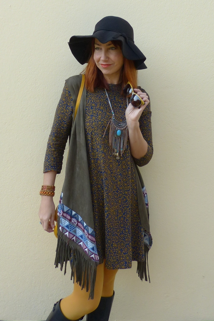 Mini dress worn with long vest, long boots, hat and tribal necklace