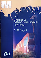 The cover of the program for Gallery M's Inaugural Open Contemporary Prize 2016 exhibition depicting the striking orange facade of the Marion Cultural Centre at night. The Gallery's logo featuring a large M is at the top left corner; the SALA logo is at the bottom left corner.