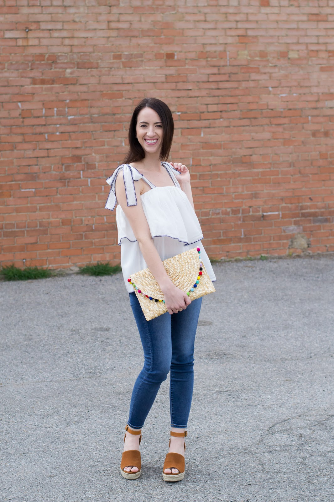 Summer style in white ruffle top with bow ties and straw pom pom clutch