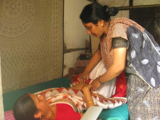 Midwife Doctor examines pregnant woman in India
