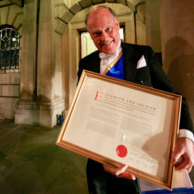 A photo of a member of the Worshipful Company of Information Technologists holding a framed facsimile of the Royal Charter granted to that Company in June 2010.