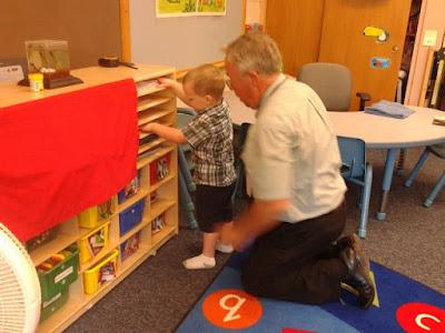 Berniukas tyrinėja lentynas, jam padeda tiflopedagogas